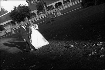 bride and groom strolling hand-in-hand with long shadows