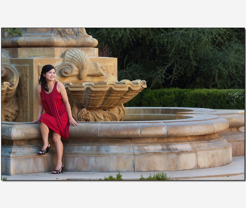 Asian-American woman posing on a fountain