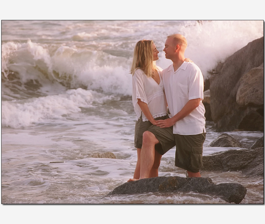 couple un-nerved waves crashing behind | engagement photos
