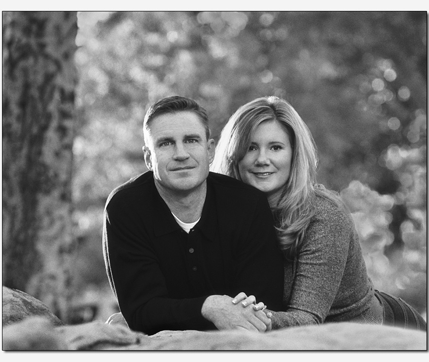 on-location couple laying on boulder forested park